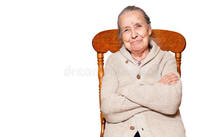 Ståenden av den gråhåriga äldre kvinnan, farmodern som sitter på brun stol för tappning, isolerar vit bakgrund Begrepp av omsorg, royaltyfri foto