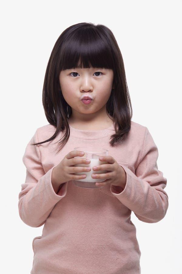 Ståenden av den gulliga flickan med smällar som dricker ett exponeringsglas av, mjölkar och gör en framsida, studioskott fotografering för bildbyråer