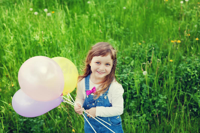 Ståenden av den gulliga lilla flickan med den hållande leksaken för det härliga leendet sväller i handen på blommaängen, lycklig  royaltyfri bild