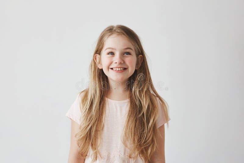 Ståenden av den gulliga lilla flickan med långt ljust hår som brightfully som ler ser översidan på färgrikt flyg, sväller med royaltyfri foto