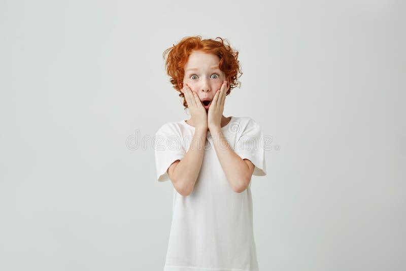 Ståenden av den gulliga lilla rödhårig manpojken med fräknar i den vita t-skjortan som var upphetsad med den nya videospelet, som royaltyfri foto