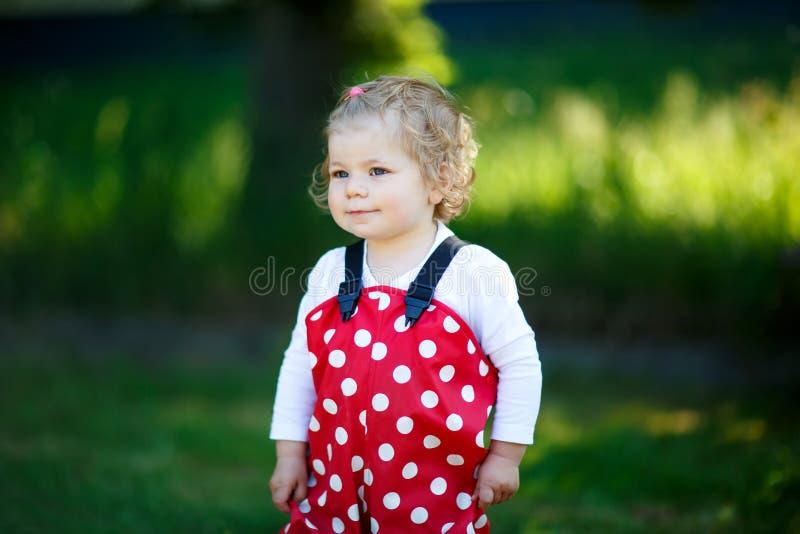 Ståenden av den gulliga litet barnflickan som utomhus spelar härligt, behandla som ett barn i byxa för rött gummi som har gyckel  royaltyfria foton