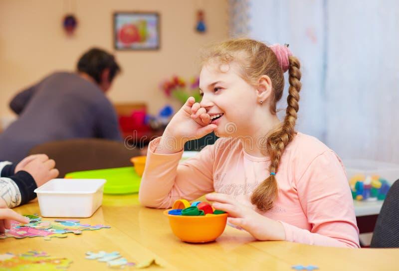 Ståenden av den gulliga lyckliga flickan med handikapp framkallar den fina motoriska expertisen på rehabiliteringmitten för ungar fotografering för bildbyråer