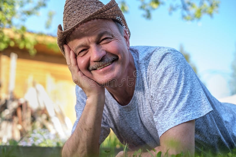 Ståenden av den härliga äldre mannen ligger på gräset som ler och ser kameran arkivbild
