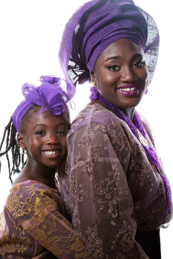 Ståenden av den härliga afrikanska damen och lilla flickan i traditiona klär isolerat royaltyfri bild