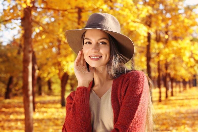Ståenden av den härliga bärande hatten för den unga kvinnan parkerar in royaltyfria foton