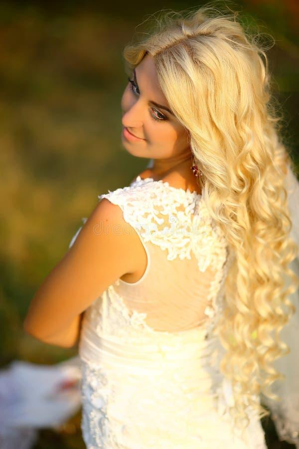Ståenden av den härliga blonda bruden med skyler i hand, med den eleganta frisyren och makeup som bär den lyxiga bröllopsklänning royaltyfri foto