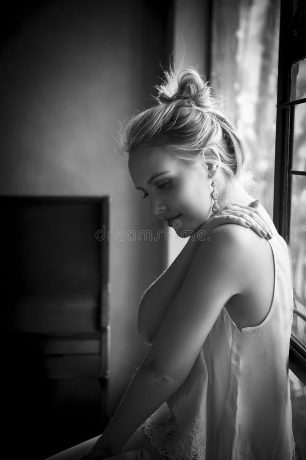 Ståenden av den härliga blonda kvinnan förlorade i tanke i svartvit monokrom arkivfoton