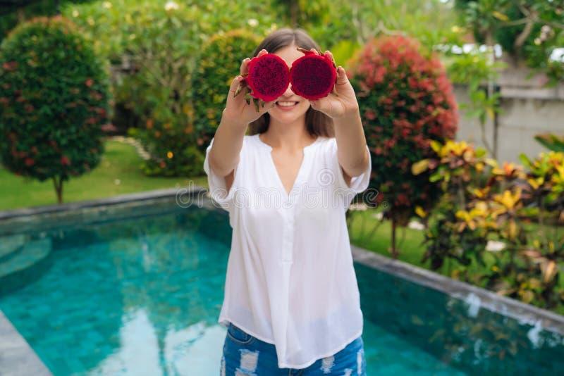 Ståenden av den härliga flickan gör ögon med två stycken av drakefrukter, pitaya arkivbild