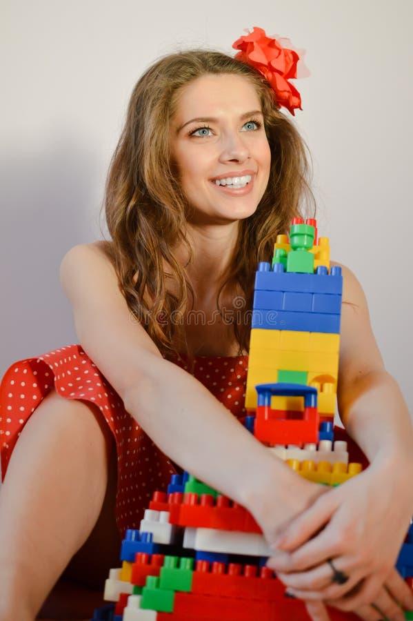Ståenden av den härliga flickan med stora tand- blekmedeltänder ler i den röda prickklänningen som har gyckel som spelar med leks arkivbilder