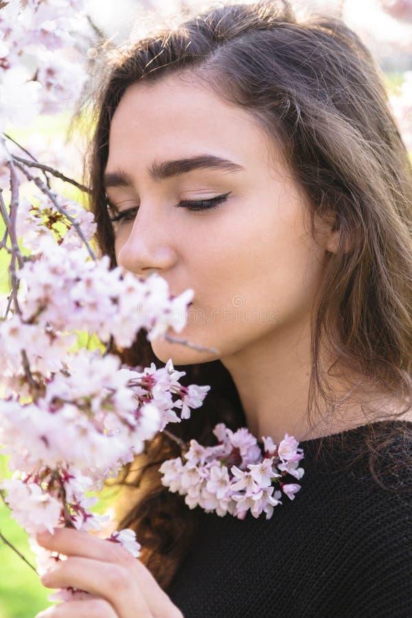 Ståenden av den härliga flickan sniffar blomma filialen fotografering för bildbyråer