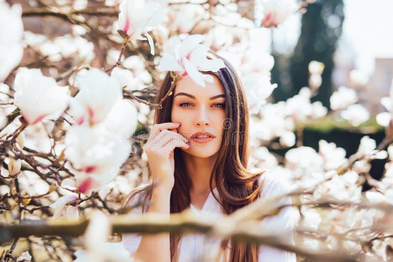 Ståenden av den härliga kvinnan kopplar av i den härliga trädgården av rosa magnolior som blomstrar på vårsäsong arkivfoto