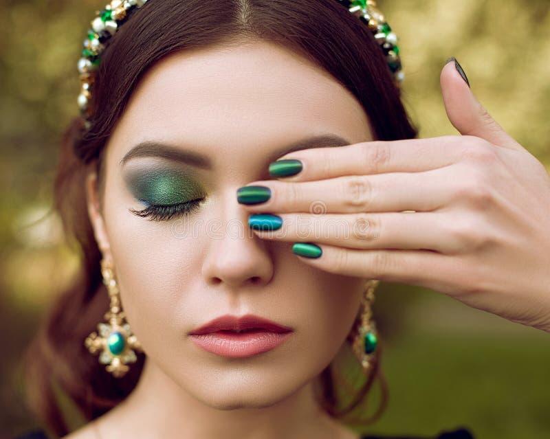 Ståenden av den härliga kvinnan, makeup och manikyr i samma utformar, smycken med ädelstenar Makeup och manicure arkivbilder