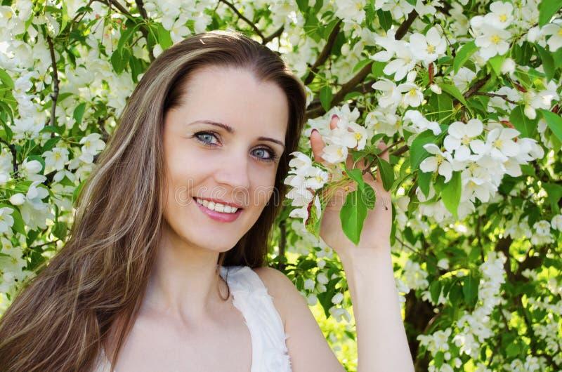 Ståenden av den härliga kvinnan med äppleträdet blommar royaltyfri bild