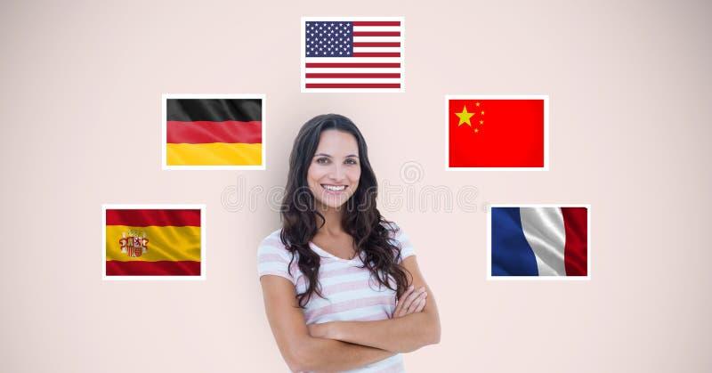 Ståenden av den härliga kvinnan med armar korsade anseende vid flaggor mot beige bakgrund arkivbild