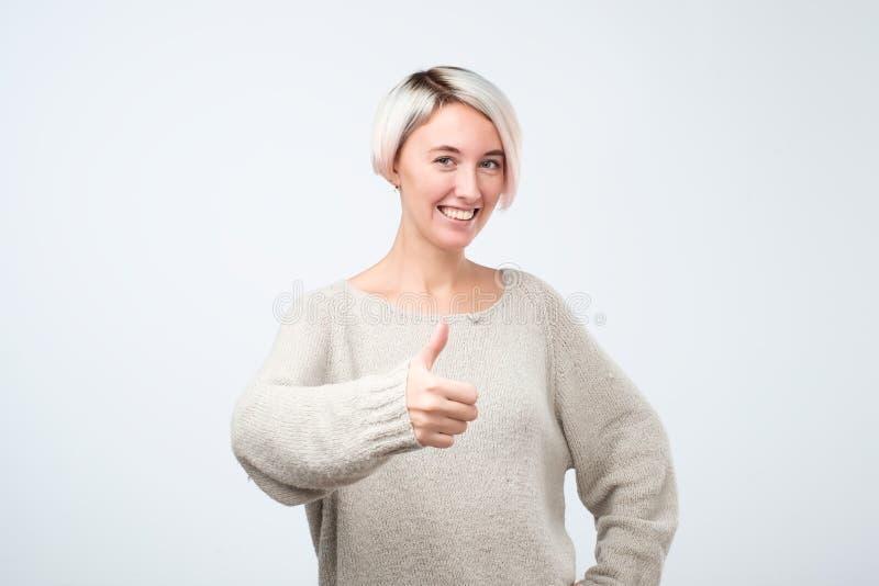 Ståenden av den härliga kvinnan med färgat kort hår med tummar up tecknet royaltyfria bilder