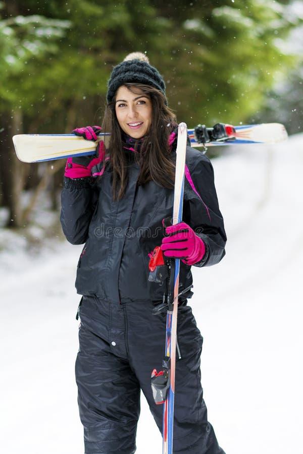 Ståenden av den härliga kvinnan med skidar och skidar dräkten i vinterberg royaltyfri fotografi