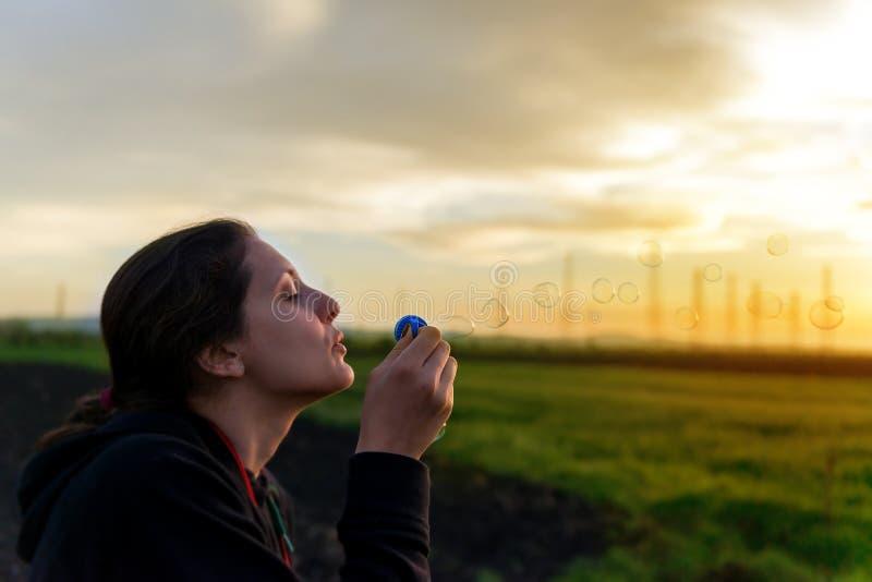Ståenden av den härliga kvinnan som blåser bubblor parkerar in arkivfoton
