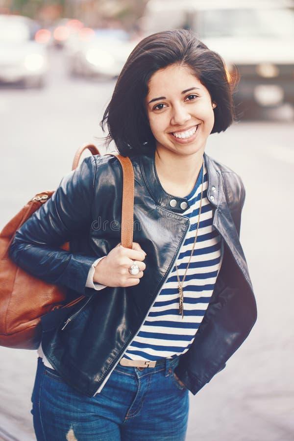 Ståenden av den härliga le unga Caucasian latinska flickakvinnan med mörk brunt synar, kort mörkt hår, i jeans, lädercyklisten arkivfoton