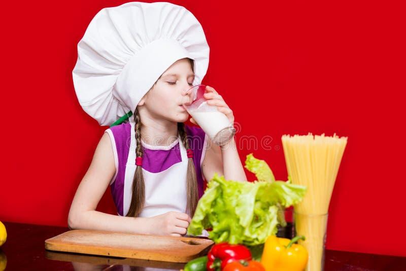 Ståenden av den härliga lilla flickan i formen av kocken som isoleras på den röda drinken, mjölkar royaltyfri bild