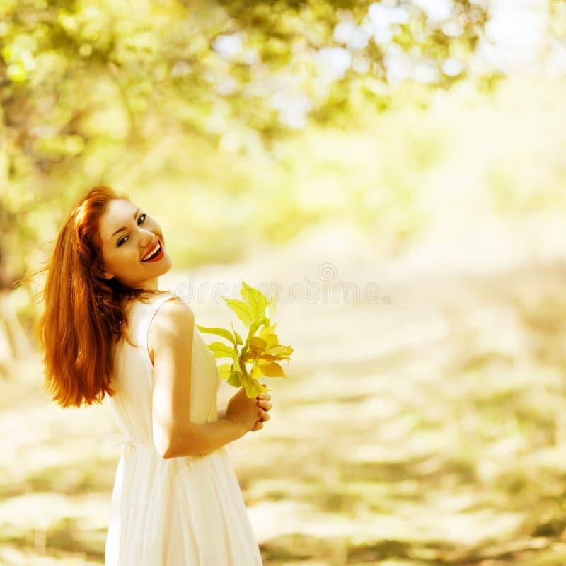 Ståenden av den härliga lyckliga ljust rödbrun flickan med guling lämnar i th fotografering för bildbyråer