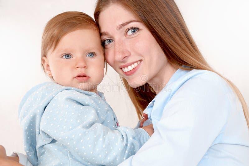 Ståenden av den härliga mamman och hon behandla som ett barn i sovrum arkivfoton