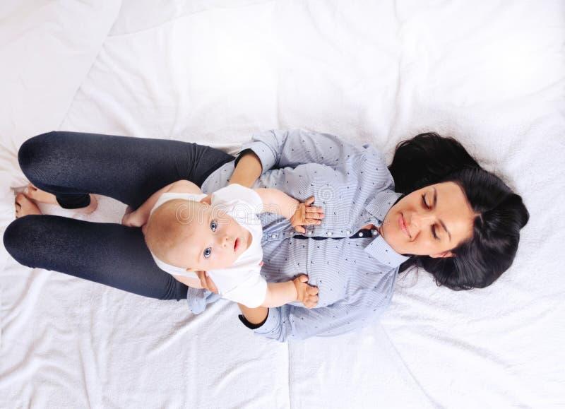 Ståenden av den härliga mamman som spelar med henne, behandla som ett barn i sovrum fotografering för bildbyråer
