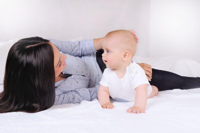 Ståenden av den härliga mamman som spelar med henne, behandla som ett barn i sovrum royaltyfria bilder