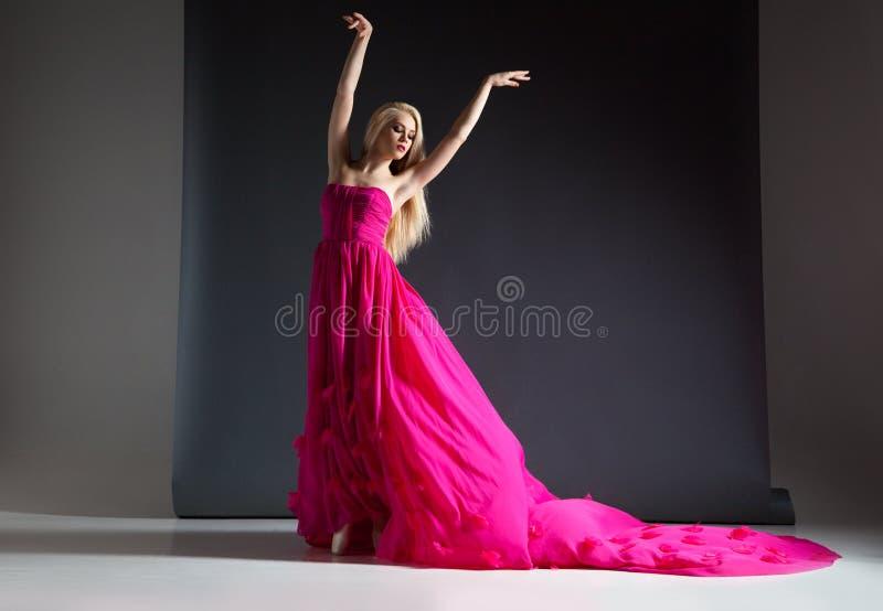 Ståenden av den härliga och eleganta blonda kvinnan som poserar i rosa färger, klär fotografering för bildbyråer
