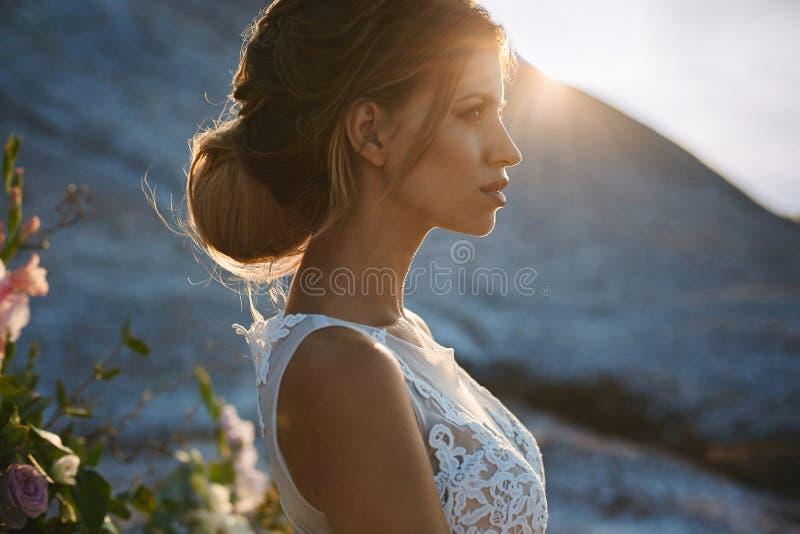 Ståenden av den härliga och sinnliga blonda modellflickan med att modellera den stilfulla frisyren i trendig vit snör åt klänning royaltyfri foto
