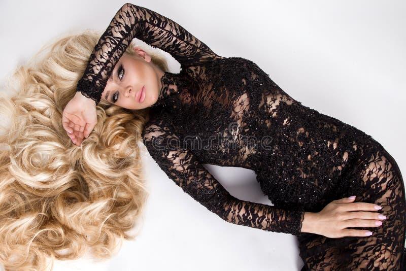 Ståenden av den härliga sexiga modellen för den unga kvinnan med lång volym för blont hår som förbluffar ögon, iklätt långt, snör arkivbilder