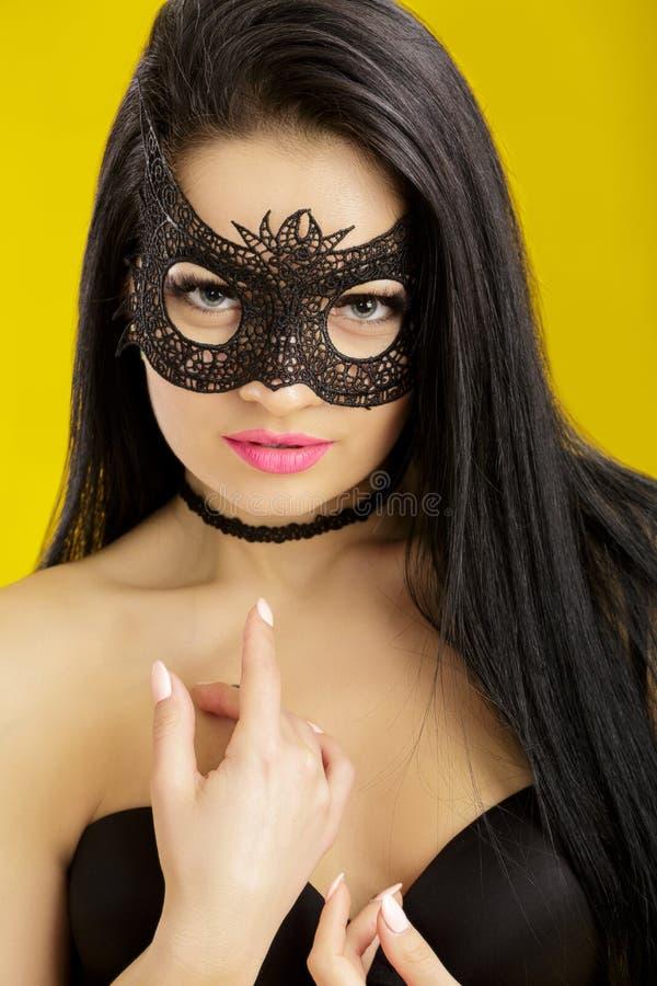 Ståenden av den härliga sinnliga kvinnan i svart snör åt maskeringen på gul bakgrund Sexig flicka i den venetian maskeringen fotografering för bildbyråer