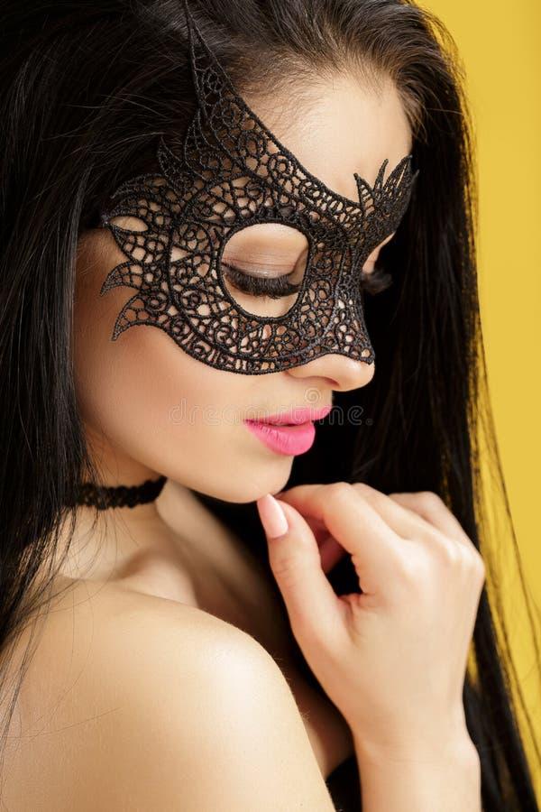 Ståenden av den härliga sinnliga kvinnan i svart snör åt maskeringen på gul bakgrund Sexig flicka i den venetian maskeringen arkivbilder