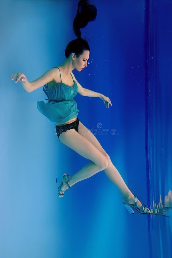 Ståenden av den härliga slanka stilfulla brunetten i blått klär, och häl skor undervattens- arkivfoto