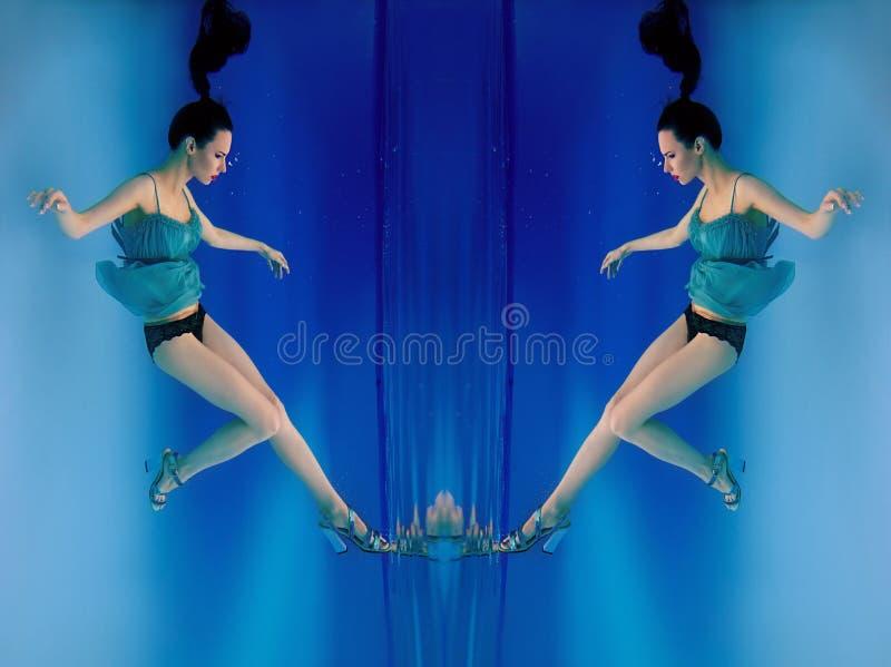 Ståenden av den härliga slanka stilfulla brunetten i blått klär, och häl skor undervattens- fotografering för bildbyråer