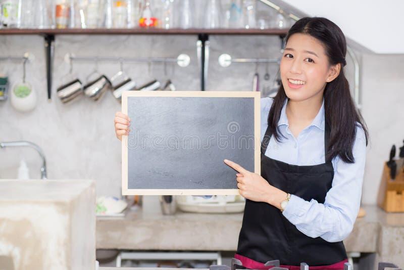 Ståenden av den härliga unga baristaen, den asiatiska kvinnan är en stående hållande svart tavla för anställd royaltyfria bilder