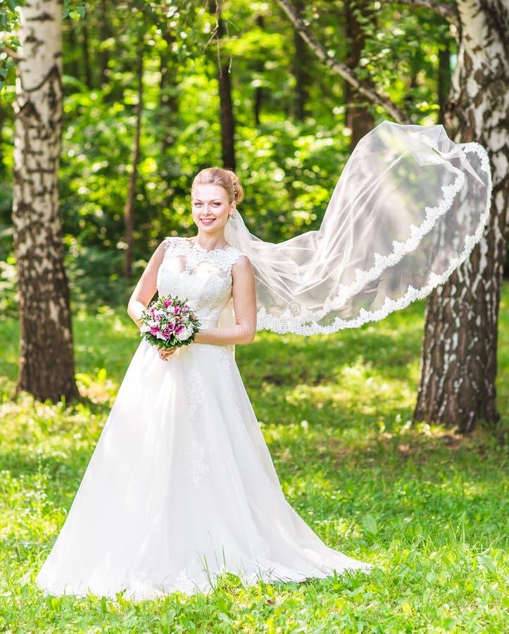 Ståenden av den härliga unga bruden i elegant vit klänning med länge skyler utomhus royaltyfria foton