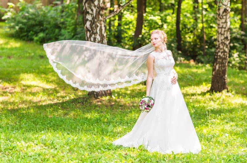 Ståenden av den härliga unga bruden i elegant vit klänning med länge skyler utomhus arkivbild