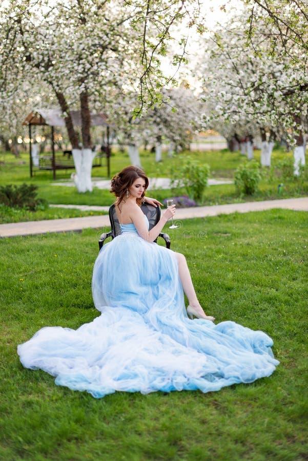 Ståenden av den härliga unga bruden som dricker champagne som poserar i parkera eller trädgården i blått, klär utomhus på ett lju royaltyfri bild