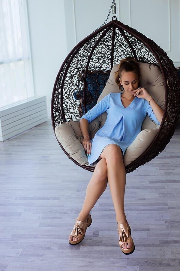 Ståenden av den härliga unga brunettkvinnan i blått klär med sminket och hästsvansen som sitter i stor stol royaltyfri foto