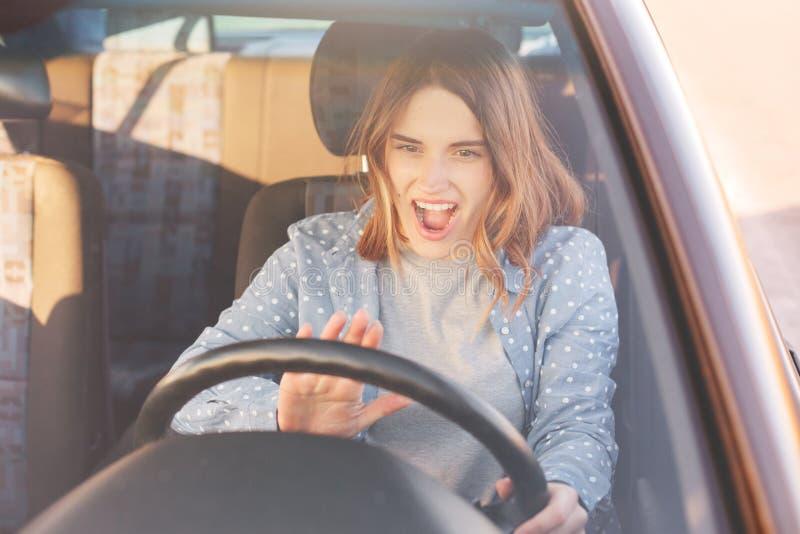 Ståenden av den härliga unga kvinnan i ny bil som happillly kör hennes första tid för bilen, tonsignaler till hennes make, har un royaltyfria bilder
