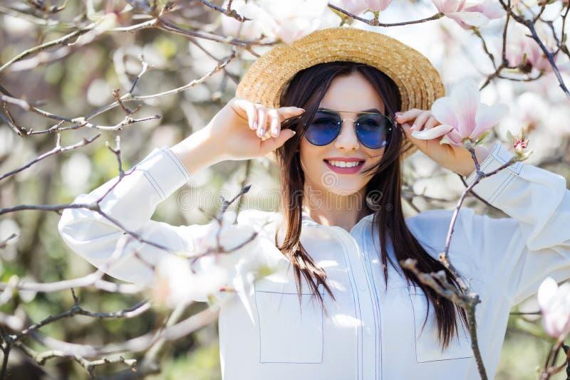 Ståenden av den härliga unga kvinnan i sommarhatt och solglasögon med magnolian blommar trädet royaltyfri foto