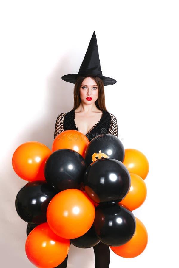 Ståenden av den härliga unga kvinnan i den svarta häxahalloween dräkten med apelsinen och svart sväller över vit bakgrund royaltyfri bild
