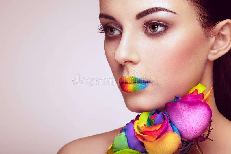 Ståenden av den härliga unga kvinnan med regnbågen steg arkivbilder