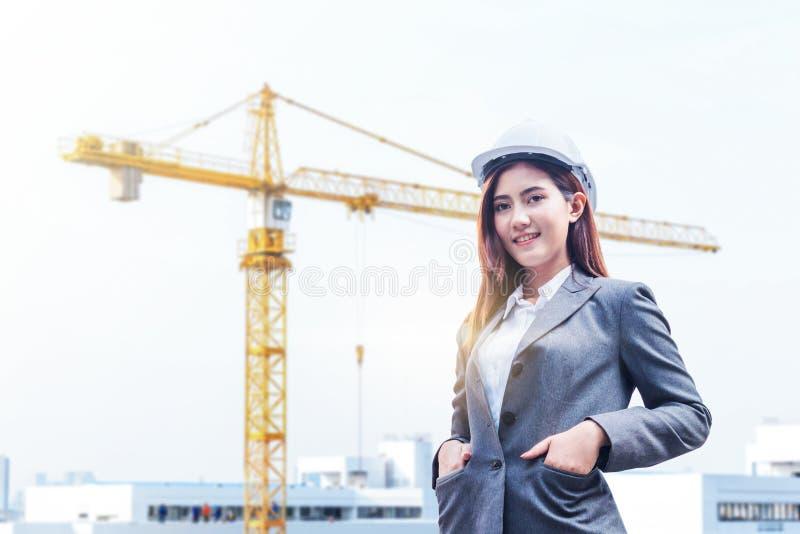 Ståenden av den härliga unga teknikerkvinnan bär en vit säkerhetshjälm som ler med förpliktelse till framgång på konstruktionspla arkivfoto