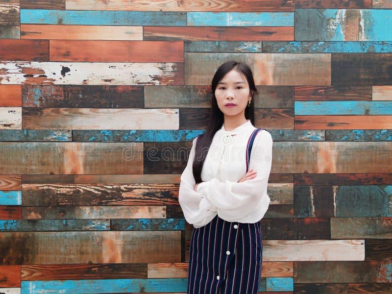 Ståenden av den kinesiska affärskvinnan i den vita skjortan som ser kameran med armar, korsade framme av den färgrika träväggen,  royaltyfri foto