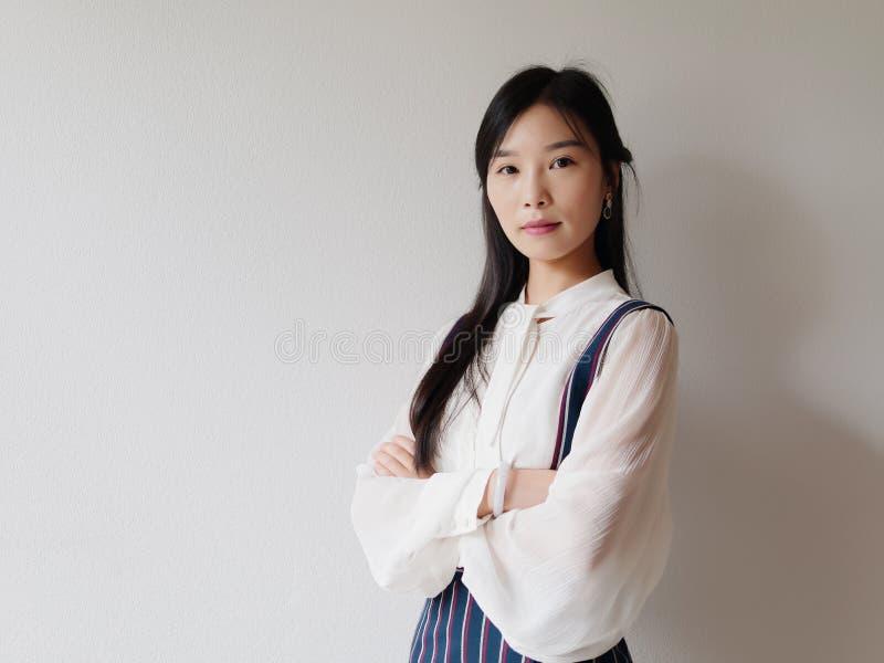 Ståenden av den kinesiska affärskvinnan i den vita skjortan som ser kameran med armar, korsade framme av den vita väggen, säker k royaltyfria bilder