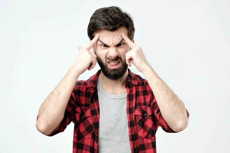 Ståenden av den koncentrerade mannen, lyfter ögonbryn med fingrar arkivfoton