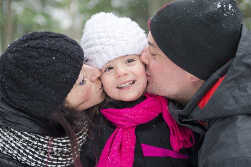 Ståenden av den kyssande moderfadern och behandla som ett barn i vinter parkerar arkivfoton