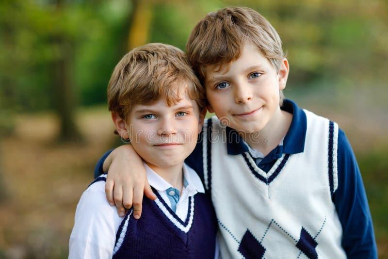 Ståenden av den lilla skolan lurar pojkar som sitter i barn, bästa vän och syskon för skog som lyckliga har gyckel på varmt royaltyfria bilder